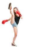 High kick with the leg. Executed by a sexy and beautiful young female fighter wearing red boxing gloves Stock Image
