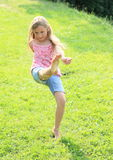 High kick. Little kid - exercising girl kicking high blades of grass Royalty Free Stock Images