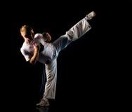 High kick pose. Man in dark practice martial art - high kick Royalty Free Stock Photos