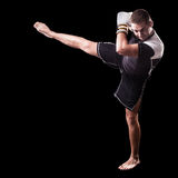 High Kick. A young kickboxer or boxer isolated over a black background Stock Photos