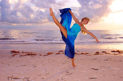 High kicking dancer. A beautiful adult female ballerina is dancing on the beach with her leg kicked up high and balanced on one foot as the sun begins to set Stock Images
