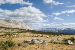 High-land meadows. View across open grassy highland meadows with stones, granite hills and clouds in Tolumne Meadows, Yosemite National Park stock photography