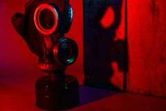 High level of danger. Military concept. A gas mask with a membrane near a wooden box in red light on which a shadow falls. Hard di royalty free stock images