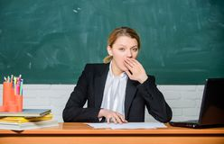 High level fatigue. Need for sleep. Exhausting work in school causes fatigue. Teacher woman sleepy face tired sit table royalty free stock photos
