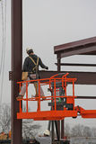 High Lift Worker. Steel worker bolting together steel beams for new building Stock Image