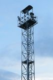 High lighting tower with observation platform at the top against a blue sky with clouds Stock Photo