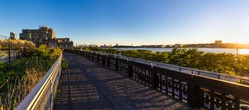 The High Line promenade at sunset with the Hudson River. Chelsea, Manhattan, New York City. Summer panoramic view from the High Line promenade at sunset with the royalty free stock photography
