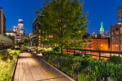 The High Line at twilight. Chelsea. Manhattan, New York City. High Line promenade at twilight with city lights and illuminated skyscrapers. Chelsea, Manhattan stock image
