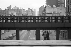 High Line View. A couple stops to look out onto the New York City streets via one of the observation areas on the famous High Line.  Taken on a dismal day in Royalty Free Stock Photography