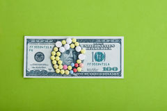 High medical cost. Pills and tablets on top of US paper currency Stock Image