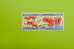 High medical cost. Pills and tablets on top of US paper currency Stock Photos