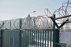 High metal fence with a sharp barbed wire on the top covered by snow in winter as a symbol of restricted access and protection of Stock Photo