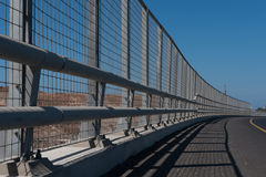 High metal guardrail along an empty highway. A perspective of a high guardrail along an empty highway. Blue sky Stock Photography