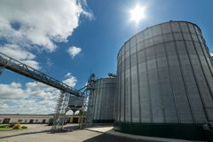 High metal silos for storage of wheat and barley. Sunny day, the blue sky. Industrial landscape Stock Image