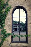 A high mirror window in an old house in which another building is reflected. The walls are covered with ivy. High mirror window in an old house in which another Royalty Free Stock Photo