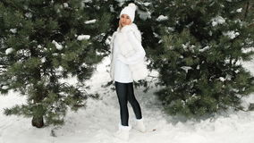 High model posing in a white dress in a green tree in the winter. The blonde woman wearing a white cap with pompons of different colors, a long woolen sweater stock video