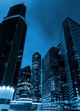 High of the modern business skyscrapers at night, the view from below. Blue tone stock photo