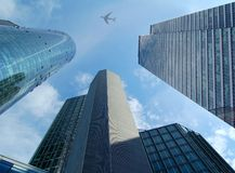 High modern skyscrapers and airplane. On the background of the blue sky Stock Image
