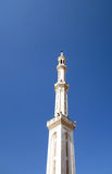 High mosque minaret. White mosque with high minaret against pure blue sky Royalty Free Stock Images