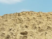 High mound of earth sand day time under sun light against blue sky with white clouds. Beautiful nature scenery Royalty Free Stock Images