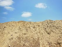 High mound of earth sand day time under sun light against blue sky with white clouds. Beautiful nature scenery Stock Photos