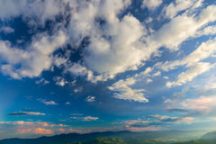 High mountain clouds on blue sky at sunset Stock Photography