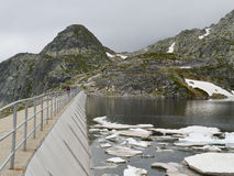High mountain dam wall in a cold sullen day Stock Image