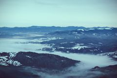 High mountain forests and hills, large plains. Mountain tops in the snow, panorama of mountain slopes and hills at sunset Royalty Free Stock Image