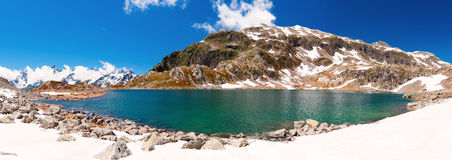 Fresh water lake in the Alps. Natural fresh water lake high in the Alps mountains with snow Royalty Free Stock Photography
