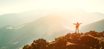 High Mountain hiker with backpack tiny figurine stands on mountain peak royalty free stock photo