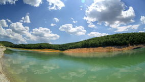 High mountain Lake with blue sky Cloudscape wide angle Time Lapse Stock Image