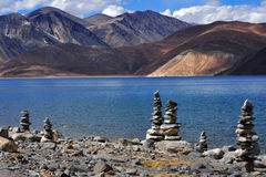 High mountain lake Pangong: in the foreground on the shore are stone Buddhist stupa, blue water lake with white clouds reflecting Royalty Free Stock Photos
