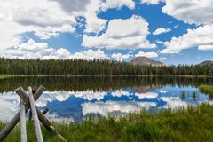 The Fence Post and Teapot Lake. High mountain lake with part of a wooden fence and reflections of the mountains and clouds on a smooth mountain lake Royalty Free Stock Images