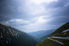 High mountain pass. A panoramic view on a cloudy day from a high overlook of a mountain pass with a few piles of melting snow remaining on the distant Royalty Free Stock Image