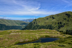 High mountain pasture and small lake in the Pyrenees mountains Stock Images