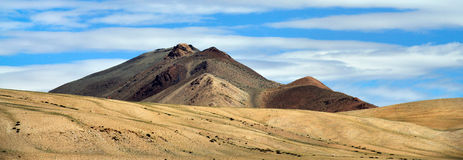High mountain peak in brown shades, illuminated by sun, blue sky with stripes of white clouds, travel through the high Himalayas,. High mountain peak in brown Stock Images