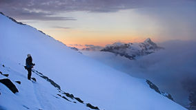 High mountain sunset. A girl is staring at the sunset over the clouds. View from Grossglockner peak, Alpes Royalty Free Stock Images