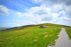 High mountain trail. Hiking trail on mountain ridge and cottage under nice puffy clouds skies,Balkan Mountains royalty free stock photo