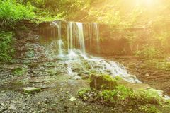 High mountain waterfall. Beautiful mountain rainforest waterfall with fast flowing water and rocks, long exposure. Natural seasonal travel outdoor background Royalty Free Stock Images
