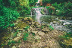 High mountain waterfall. Beautiful mountain rainforest waterfall with fast flowing water and rocks, long exposure. Natural seasonal travel outdoor background in Stock Image