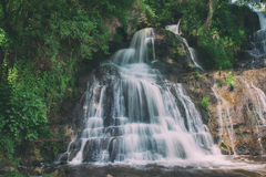 High mountain waterfall. Beautiful mountain rainforest waterfall with fast flowing water and rocks, long exposure. Natural seasonal travel outdoor background in Stock Photos