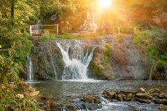 High mountain waterfall. Beautiful sunny mountain rainforest waterfall with fast flowing water and rocks, long exposure. Natural seasonal travel outdoor Stock Image