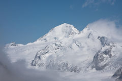 High mountains. Snow covered mountains against a blue sky in the swiss alps Stock Image