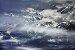 High mountains, closed by white mist strips and clouds, peaks in snow. High mountains, closed by white mist strips and clouds, peaks in the snow Royalty Free Stock Photos