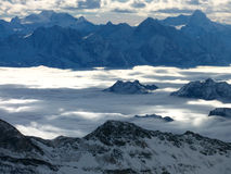 High mountains between cloud layers. High alpine mountain tops peeking through cloud layers to be covered by even higher clouds royalty free stock images