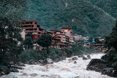 High mountains in the clouds and river in Aguas Calientes city. A river flows against a background of a mountain in the clouds in Aguas Calientes village stock photos