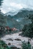High mountains in the clouds and river in Aguas Calientes city. A river flows against a background of a mountain in the clouds in Aguas Calientes village stock photo