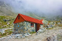 High mountains cottage for tourist and climbers rest. On cloudy background Stock Image