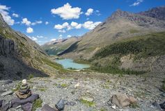 High in the mountains flowing river and flows into the lake. Around the blue sky and mountains Stock Photography