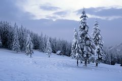 High on the mountains in the forest covered with snow there is lonely old wooden hut. Stock Photo